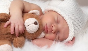 Cute-Sleeping-Newborn-Baby-With-Teddy-Bear-600x350